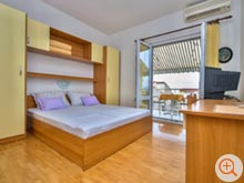 The comfortable queen size bed is right next to the door to the balcony of the holiday home More.