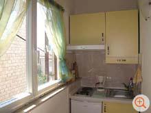 the kitchenette of Riba with stove, exhaust hood, coffee machine and fridge with freezer